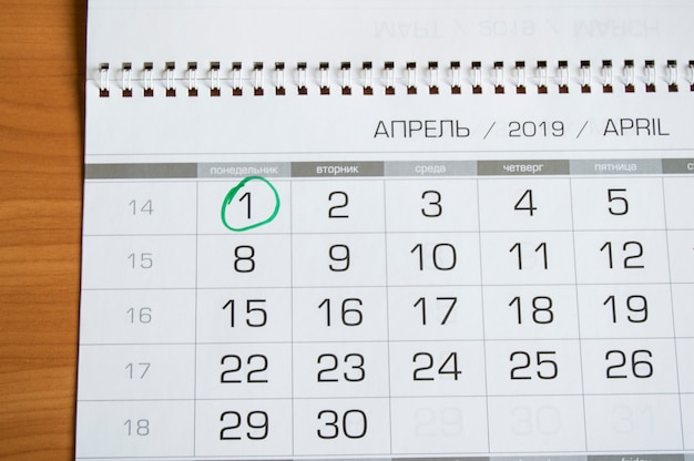Wandkalender mit dem monat april, 1. april - aprilscherz, eingekreist mit einem grünen kreis