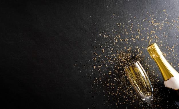 Wandkonzept der weihnachts- und neujahrsfeiertage aus champagnergläsern mit goldenem glitzer auf schwarzer holzwand.