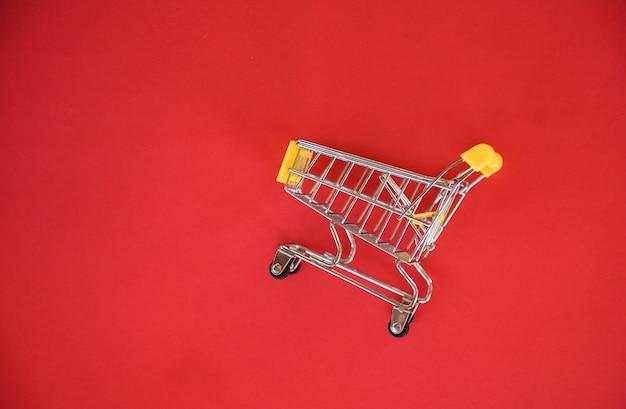 Warenkorb auf rotem hintergrund / online-shopping-konzept mit gelbem einkaufswagen auf draufsicht - einkaufsferien
