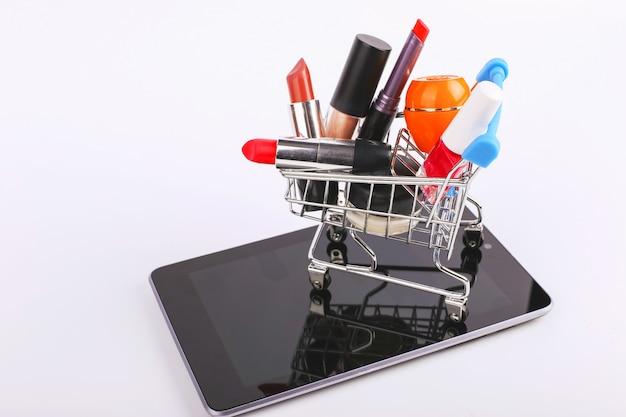 Warenkorb mit kosmetik ist auf dem smartphone. online-verkaufskonzept.