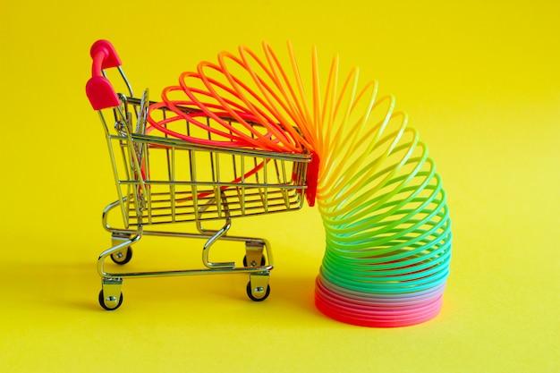 Warenkorb mit plastikspielzeug-regenbogenspirale