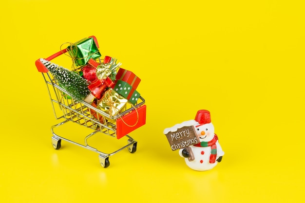 Warenkorb mit weihnachtsbaum und miniaturgeschenkboxen mit schneemannpuppe