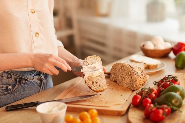 Warm getönte nahaufnahme der nicht wiedererkennbaren frau, die sandwiches macht, während frühstück in der gemütlichen küche zubereitet