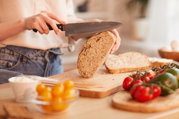Warm getönte nahaufnahme der unerkennbaren frau, die frisches vollkornbrot schneidet, während frühstück in der gemütlichen küche macht
