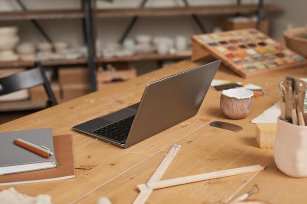 Warm getöntes hintergrundbild des laptops auf holztisch in leerer töpferwerkstatt, kleinunternehmenskonzept, kopierraum
