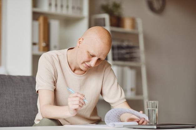 Warm getöntes porträt der erwachsenen kahlen frau, die patientenform in der arztpraxis während alopezie und krebswiederherstellung ausfüllt, kopieren raum