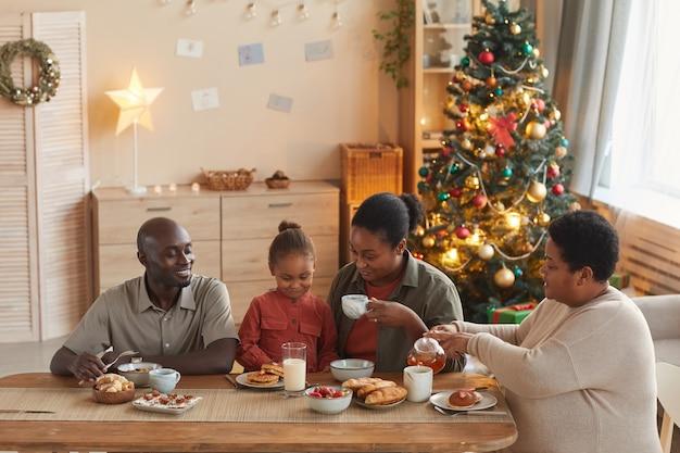 Warm getöntes porträt der glücklichen afroamerikanischen familie, die tee und snacks genießt, während weihnachten zu hause im gemütlichen innenraum, kopierraum feiert