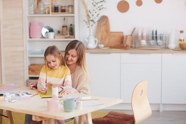 Warm getöntes porträt der glücklichen mutter, die kleine tochter umarmt, während bilder am holztisch in der küche malen, raum kopieren