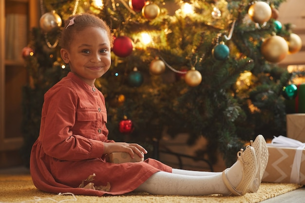 Warm getöntes porträt des lächelnden afroamerikanischen mädchens, das weihnachtsgeschenke öffnet, während am baum zu hause sitzen, raum kopieren