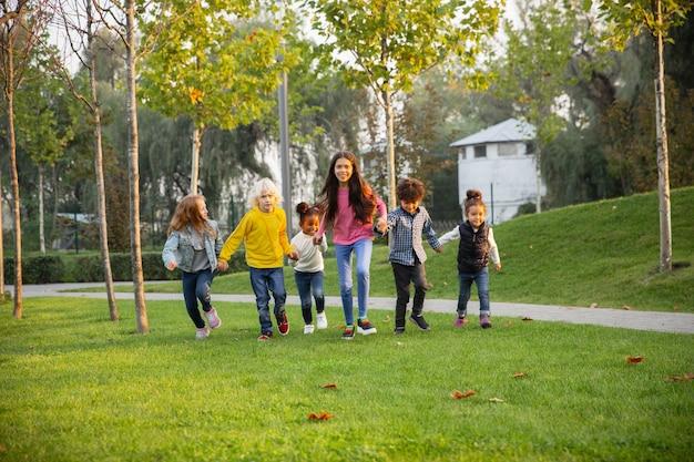 Warm. interracial gruppe von kindern, mädchen und jungen, die zusammen im park am sommertag spielen.