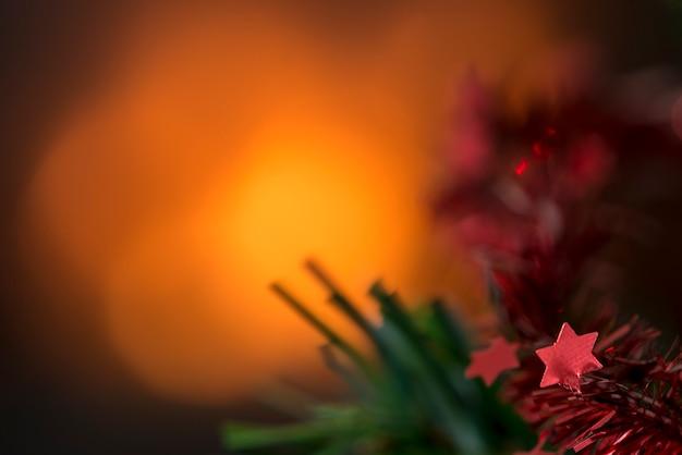 Warm leuchtender weihnachtshintergrund mit kopienraum und fokus auf kleine rote sterne auf dem ast eines dekorierten weihnachtsbaums in der ecke.