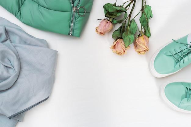 Warme damenbekleidung, daunenjacke, schuhe, schal, getrocknete rosen. modeebenenlage mit kopienraum auf weißem konkretem hintergrund. ansicht von oben.