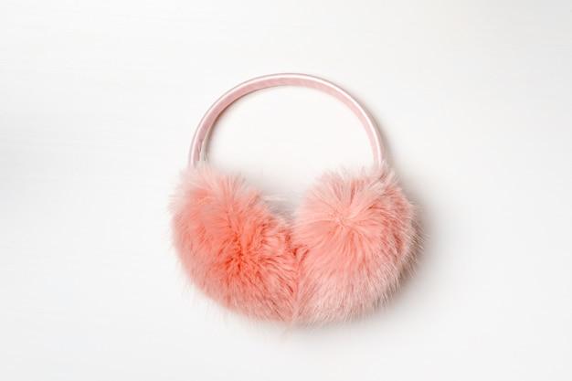 Warme flaumige rosa ohrenschützer auf einem weiß