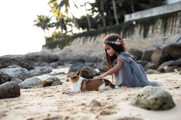 Warme fotografie eines süßen hundes und eines jugendlichen mädchens im kleid mit kranz, die sie an der küste in thailand spielen.