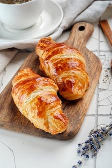 Warme frisch gebackene croissants auf dem küchentisch mit tee. französische croissants mit goldener kruste zum frühstück am morgen