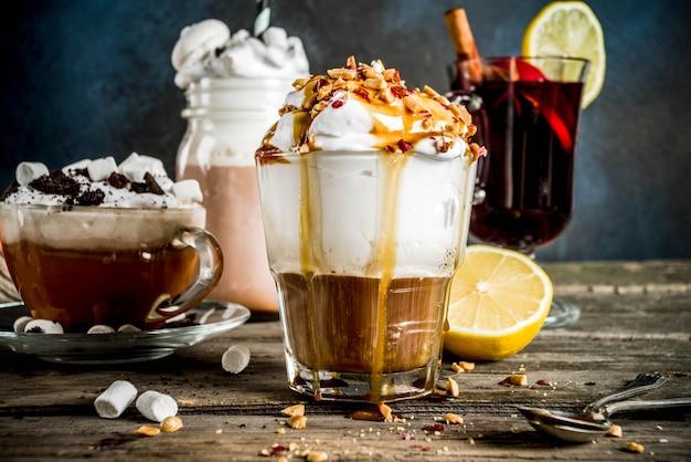 Warme getränke des herbstwinters, heiße schokolade, kürbis latte, karamell- und erdnusskaffee latte, glühwein, gemütlicher dunkler hintergrund