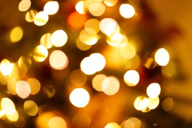 Warme goldene festliche girlande des neuen jahres beleuchtet unscharfen hintergrund