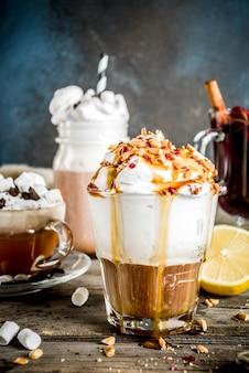 Warme herbstwintergetränke, heiße schokolade, kürbislatte, karamell und erdnusskaffee latte, glühwein