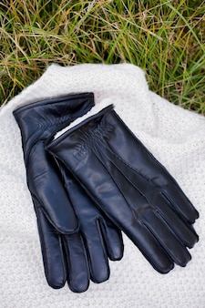 Warme herrenhandschuhe aus leder liegen im gras.