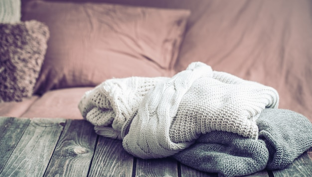 Warme kleidung, gestrickte pullover auf einem holztisch