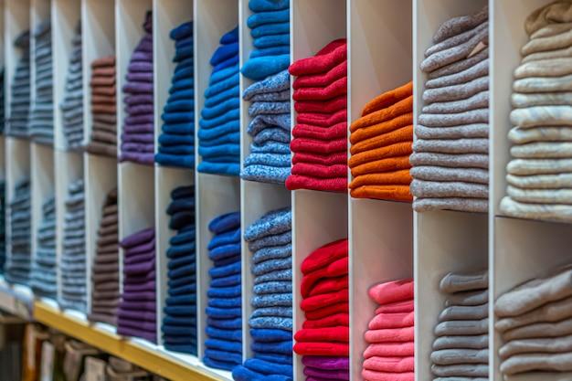 Warme kleidung ordentlich auf einem regal gefaltet. eine reihe von bunten pullovern, strickjacken, sweatshirts, pullovern, hoodies im ausstellungsraum oder im geschäft.