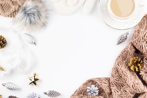 Warme, kuschelige winterkleidung, heißes getränk und weihnachtsdekoration auf weiß