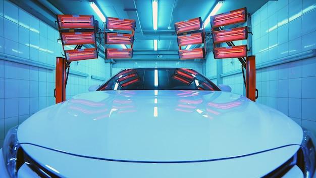 Warme rote lampen zum aushärten des keramikpolierens, vorderansicht des autos, lampen befinden sich hinter dem auto