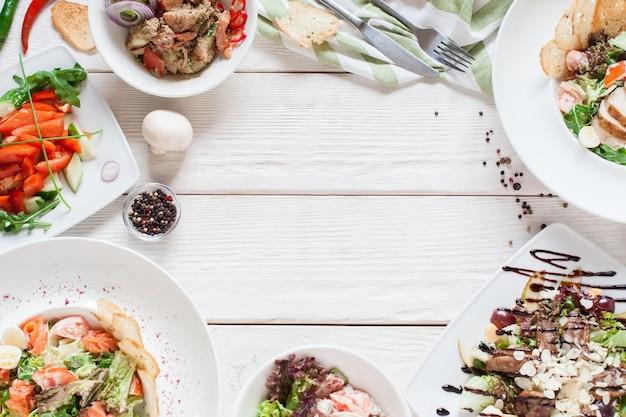 Warme salate rahmen auf weißem holz flach legen. draufsicht auf restauranttisch mit fleischsortiment