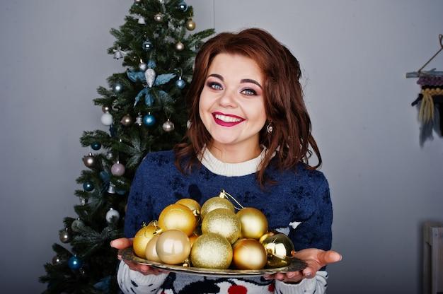 Warme strickjacke der mädchenabnutzung mit weihnachtsbaum auf studio mit weihnachtsdekorationen an den händen. frohe winterferien konzept.