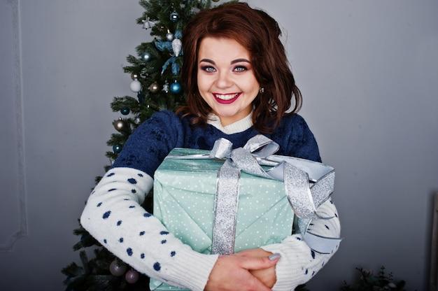 Warme strickjacke der mädchenabnutzung mit weihnachtsbaum auf studio mit weihnachtskastendekorationen an den händen. frohe winterferien konzept.