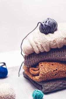 Warme strickkleidung und schlaufen des garns auf weißem hintergrund
