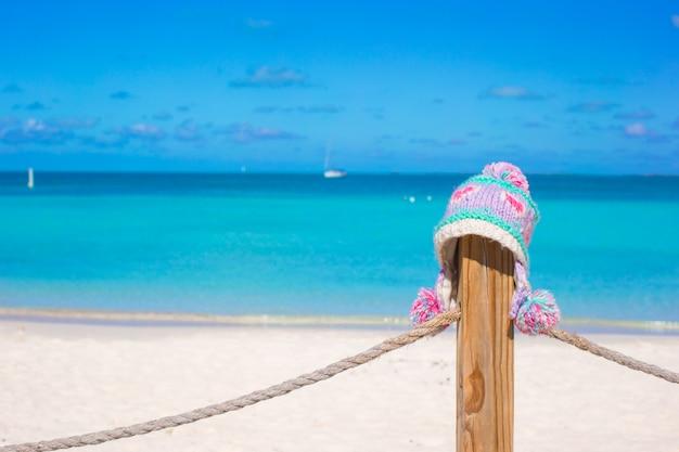 Warme strickmütze der nahaufnahme auf zaun am tropischen strand