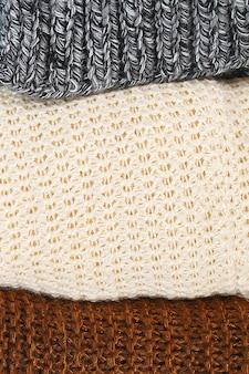 Warme strickpullover. stapel der gestrickten kleidung auf blauem hintergrund, strickjacken, strickwaren