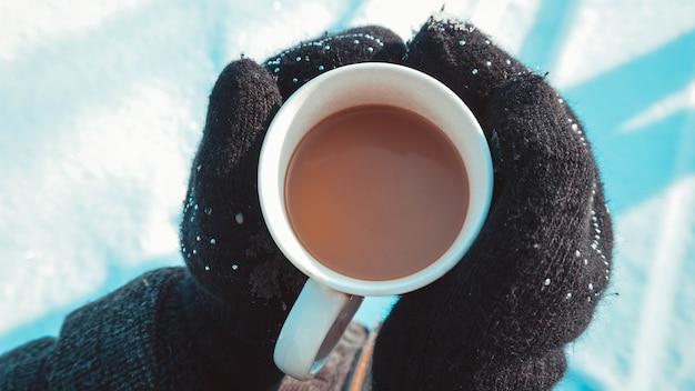 Warme tasse heißen kaffee, der sich in den händen in fäustlingen erwärmt. frauenhände auf dem hintergrund von schnee, winter