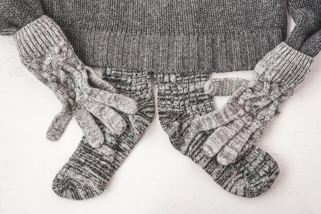 Warme weibliche graue strickhandschuhe, socken auf einem pullover auf weißem strukturiertem hintergrund. flache lage, minimalistisches modekonzept von oben.
