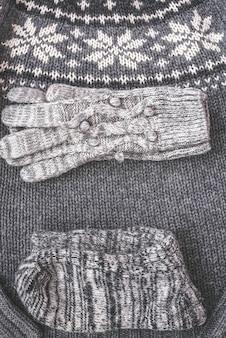 Warme weibliche graue strickhandschuhe, socken auf einem strukturierten vertikalen bannerhintergrund des pullovers. flache lage, minimalistisches modekonzept von oben.