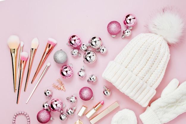 Warme winterkleidung, kosmetik und weihnachtsdekoration. anordnung in pastellrosafarben.