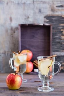 Warmer, beruhigender tee aus äpfeln und zimt in gläsern und zutaten zum kochen auf einem holztisch. detox-konzept, antidepressivum. schönes stillleben