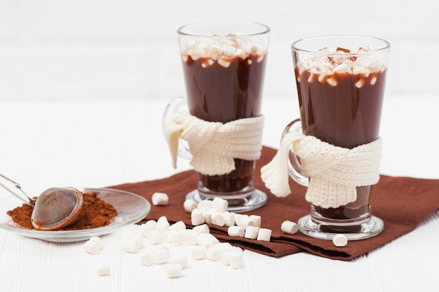 Warmer kakao in gläsern mit eibisch, braun und beige servietten auf weißem hintergrund aus holz.