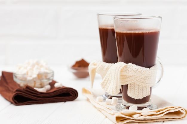 Warmer kakao in gläsern mit marshmallow-, crocahet-dekorationen, braunen und beigen servietten.
