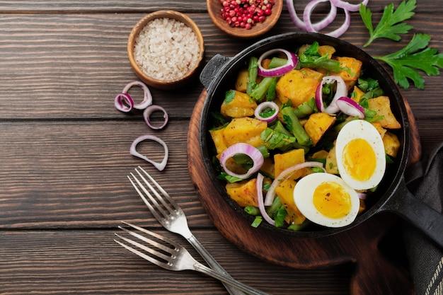 Warmer kartoffelsalat mit grünen bohnen, pfeffer, petersilie, eiern und roten zwiebeln in der pfanne auf altem holztisch. selektiver fokus. draufsicht. speicherplatz kopieren.