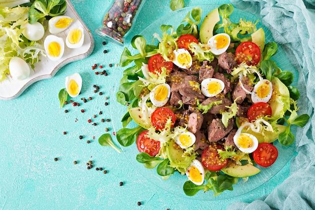 Warmer salat aus hühnerleber-, avocado-, tomaten- und wachteleiern. gesundes abendessen. diätmenü. flach liegen. ansicht von oben