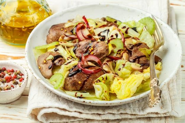 Warmer salat aus hühnerleber (ente, gans, kaninchen), eisbergsalat, roten zwiebeln, sellerie und gebratenen pilzen