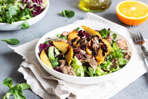 Warmer salat mit gebratener leber, karamellisierter birne, preiselbeeren und salatmischung.