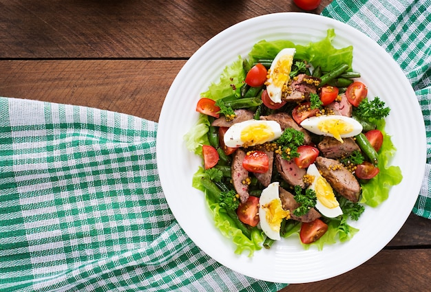 Warmer salat mit hühnerleber, grünen bohnen, eiern, tomaten und balsamico-dressing. draufsicht