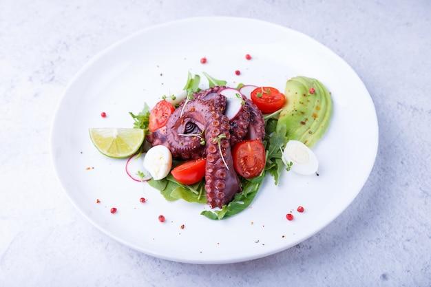 Warmer salat mit oktopus-kirschtomaten avocado rucola wachteleier rettich und limette auf einem weißen teller