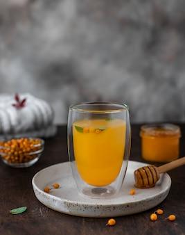 Warmer sanddorntee mit honig und minze in einem glas.
