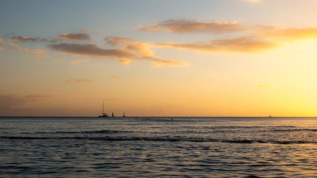 Warmer sonnenuntergang auf dem meer mit segelbooten am horizont