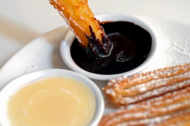 Warmer spanischer churros donut, der zu dunkler schokoladensoße taucht