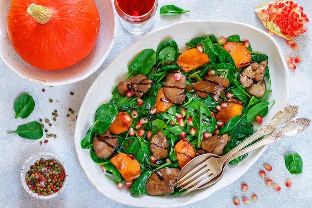 Warmer spinatsalat mit hühnerleber, gebackenem kürbis und granatapfel